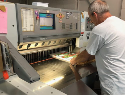 Acme Printing employee setting up his machine