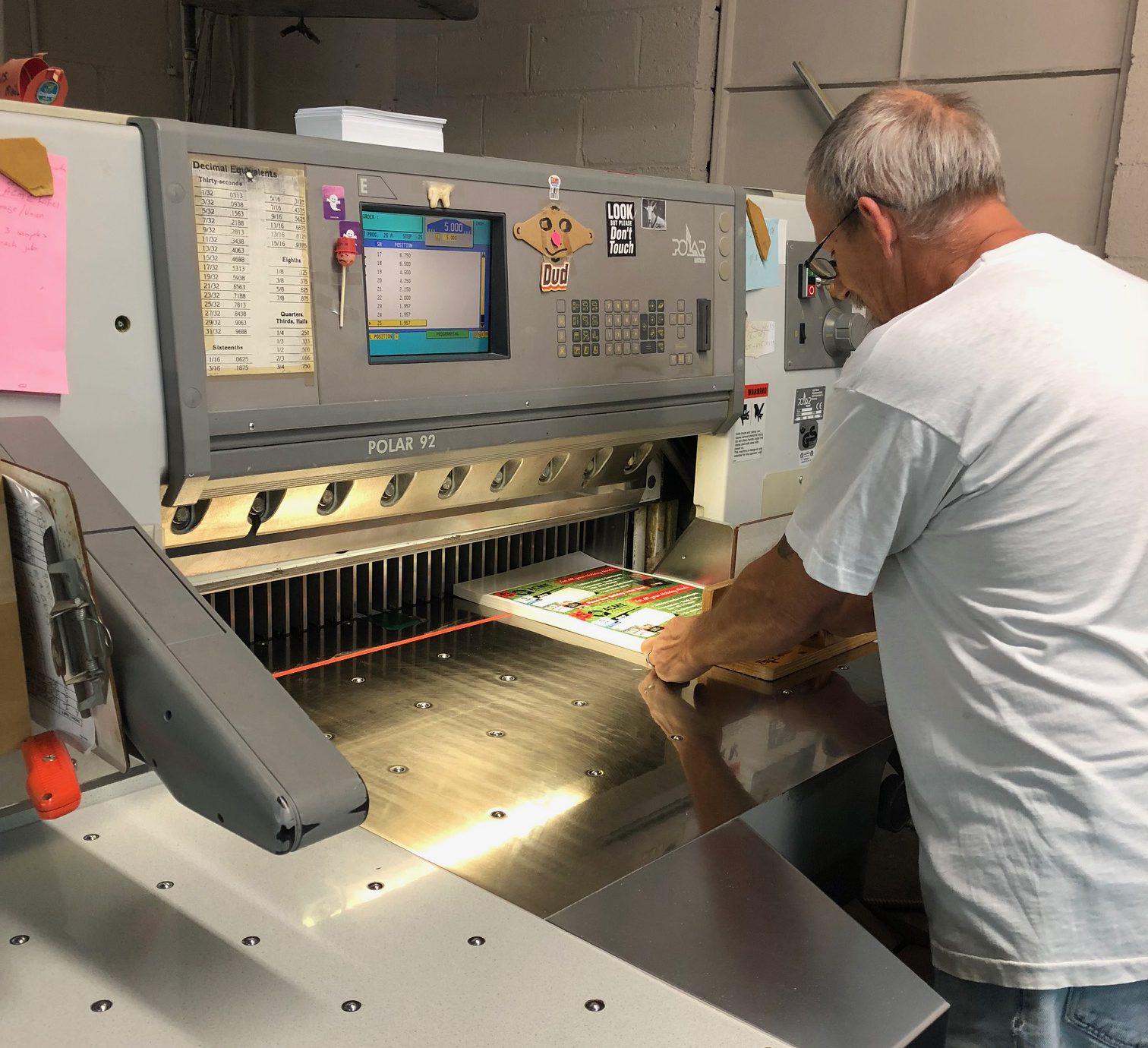 Acme Printing employee setting up his machine