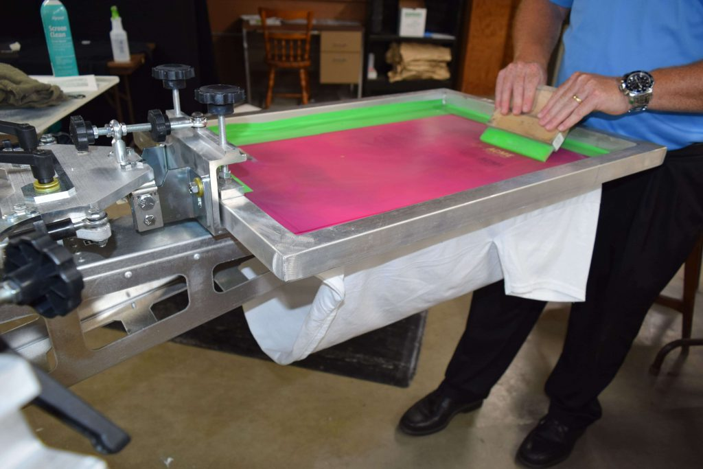 Using the manual screen press machine to add a layer of ink to the custom tshirt.