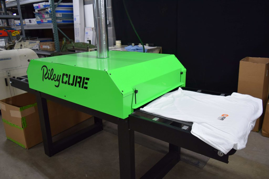 Riley Cure machine setting the ink on a custom screen printing job by Acme Printing in Morristown, TN