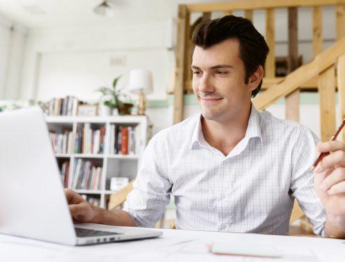 man smiling while working on laptop