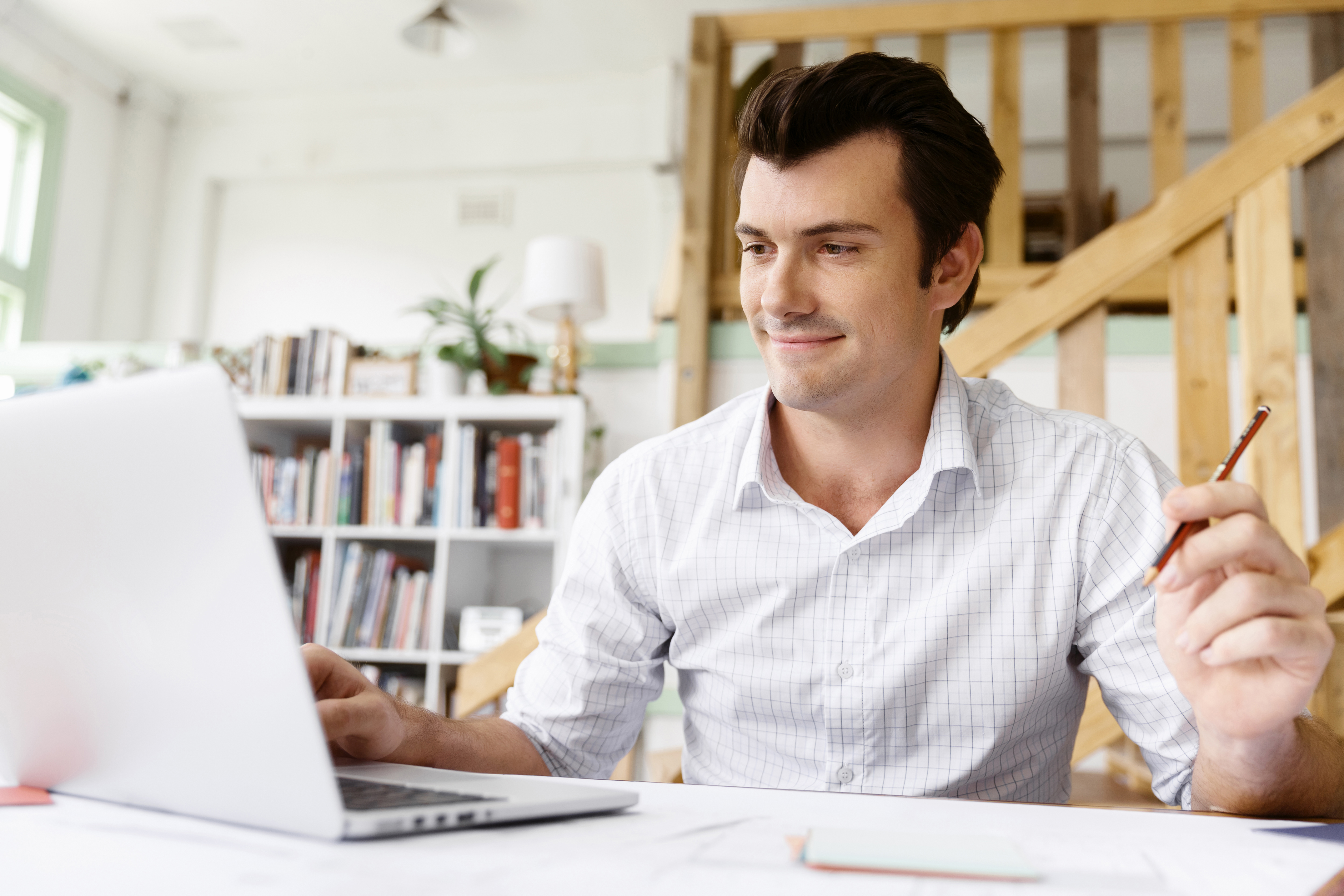 man smiling while working on laptop