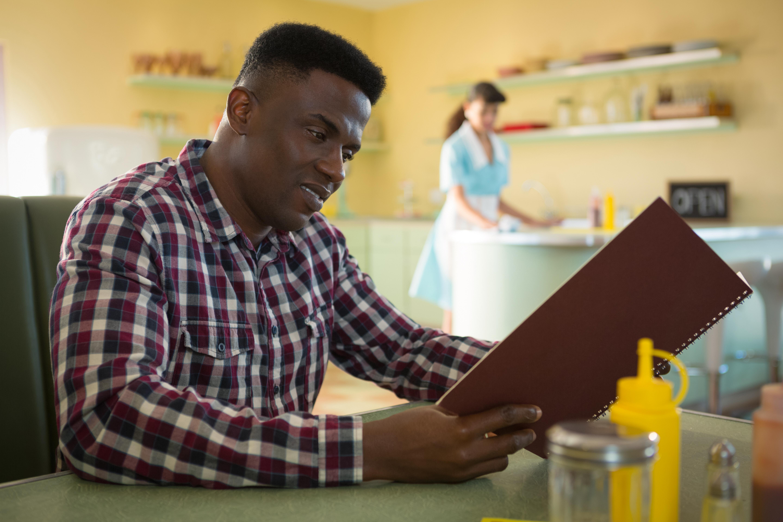 Happy man looking at menu printed by Acme in restaurant